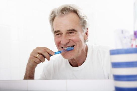 senior man brushing implant dentures